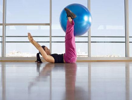 אישה מחזיקה כדור בין הרגליים שמורמות למעלה (צילום: אור גץ, jupiter images)